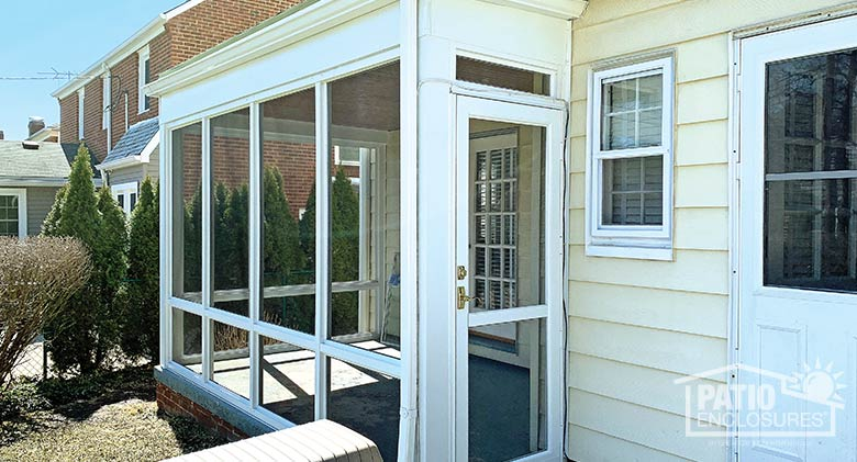 White screen room with knee wall enclosing existing covered patio.