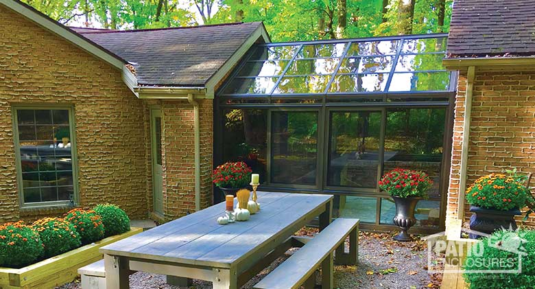 Bronze solarium with aluminum frame and gable roof.