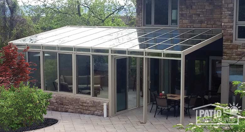 Sandstone solarium with aluminum frame and single-slope roof.