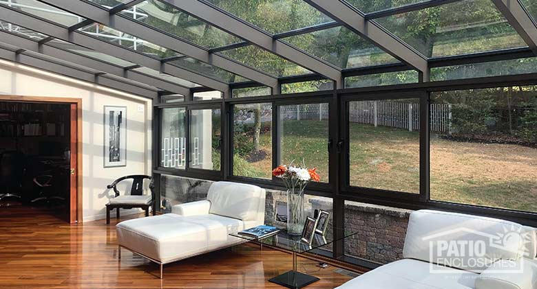 Bronze solarium with aluminum frame and single-slope roof.