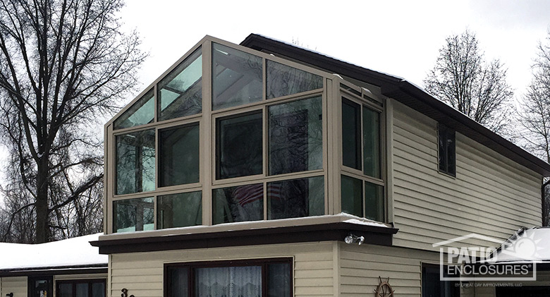 Gable roof straight eave solarium with sandstone extruded aluminum frame added to second story.