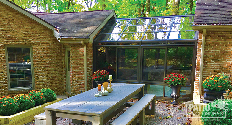 Gable roof straight eave solarium with bronze extruded aluminum frame.