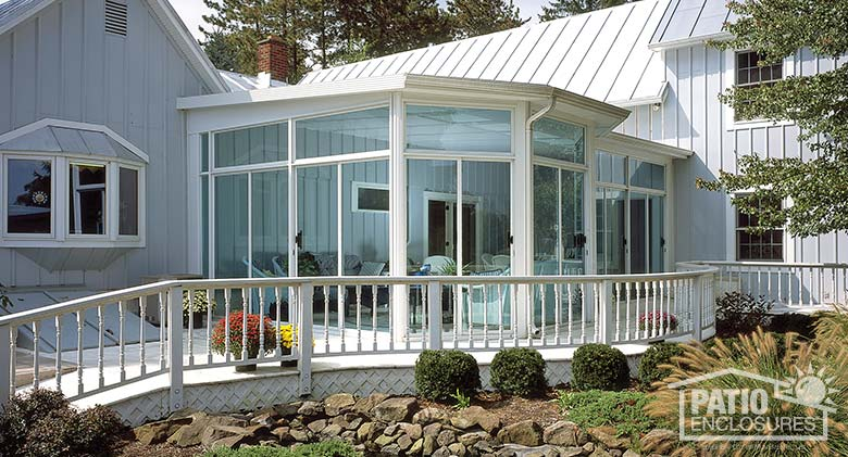 White three season sunroom with transoms and single-slope roof.