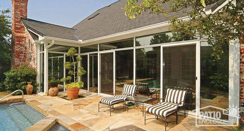White three season sunroom with transoms enclosing an existing covered patio.