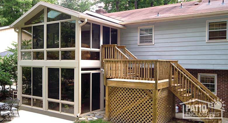 Double-decker sandstone three season sunroom with insulated glass and gable roof.