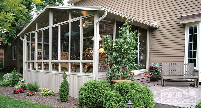 Three season sunroom with sandstone aluminum frame and gable roof.