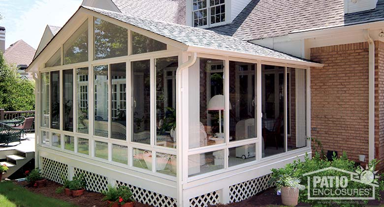 White elite three season room with glass knee walls and shingled gable roof.
