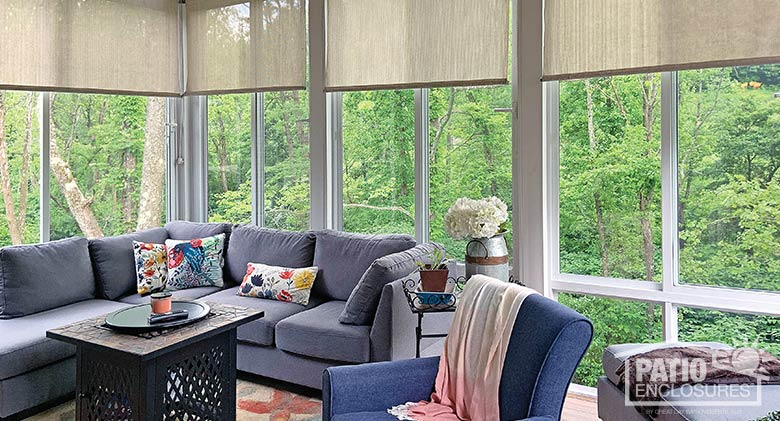 Elite three season sunroom with glass knee wall and roller shades.