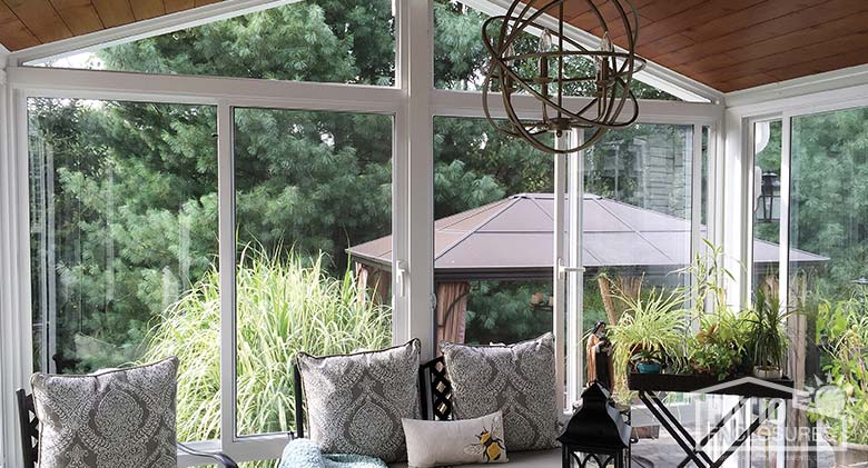 Elite three season sunroom with white aluminum frame, gable roof and custom wood ceiling.