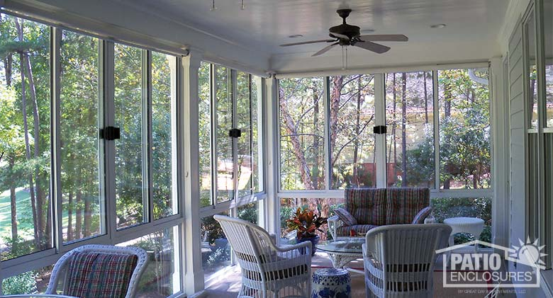 White three season sunroom enclosing an existing covered porch.