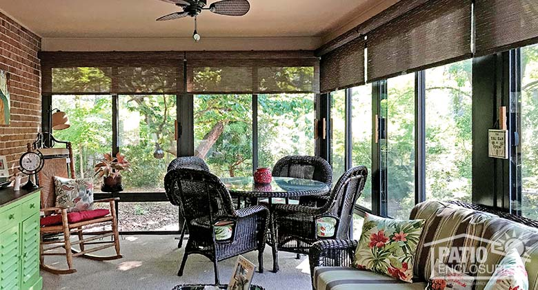 Three season room with insulated glass and roller shades enclosing an existing covered porch.