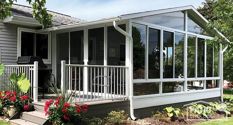 Three season sunroom with glass knee wall, gable roof and attached deck.