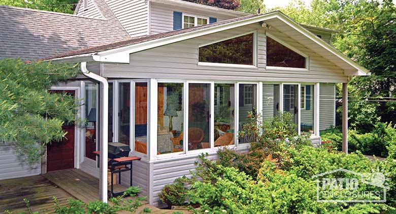 Traditional sunroom with glass wings in shingled gable roof