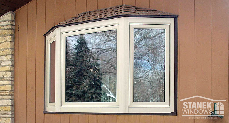 Beige bay window with shingled hip roof