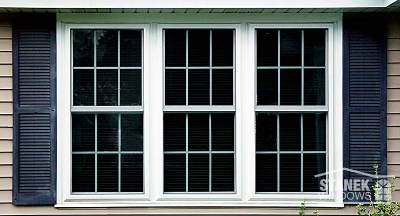 Three double-hung windows mulled together in white with interior colonial grids.