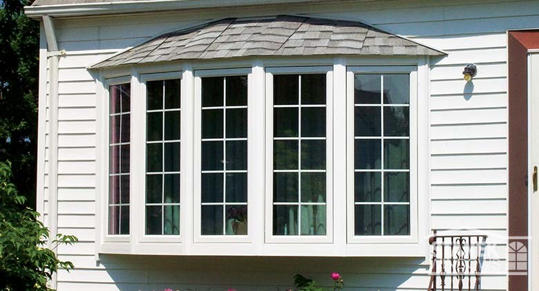 Five-lite bow window with interior colonial grids and shingled hip roof.