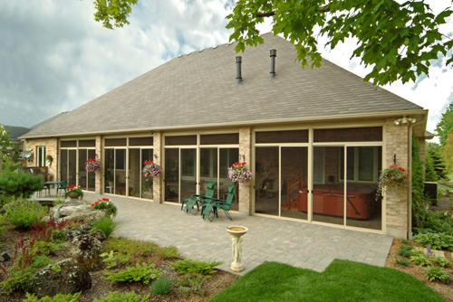 Outside View of a Very Large Sunroom Under Existing Roof As Part of a Patio